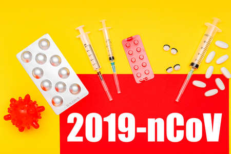 Different drugs, medicines tablets, pills, syringes against coronavirus, models of coronavirus, text on red banner 2019-nCoV on yellow background. Stock Photo