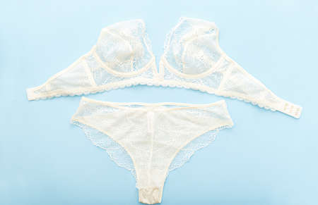 Bra and pantie. White lace lingerie on blue background. Flat lay with lace underwear. Beautiful romantic unlined elongated bralette. Set of white bra and bikini.Sale, offer, lingerie store Stock Photo