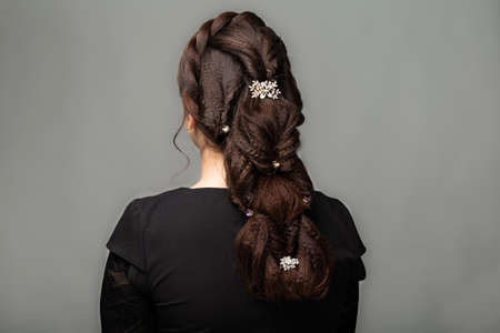 Weave, braid tail hairstyle. Hairstyle on brown hair woman with long hair on a gray background. Professional hairdressing services.Hair styling, making braid with hairpin