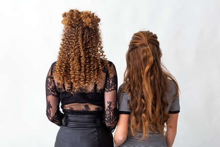 Two redhead girls with hairstyles back view. Wave curls hairstyle. Hairstyle on red brown hair womans with long hair on white background. Professional hairdressing services.Hair styling Zdjęcie Seryjne