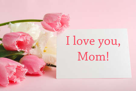 I love you Mom text on gift card in flower bouquet on pink background. Greeting card for Mom. Happy Mothers Day. Flower delivery.Congratulations card in flowers for women.Greeting card in pink tulips