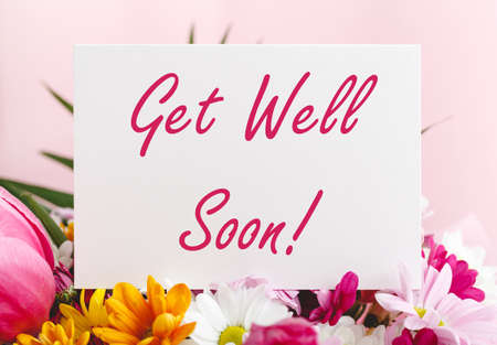 Get Well Soon card in flower bouquet on pink background. Stock photo mock up for text
