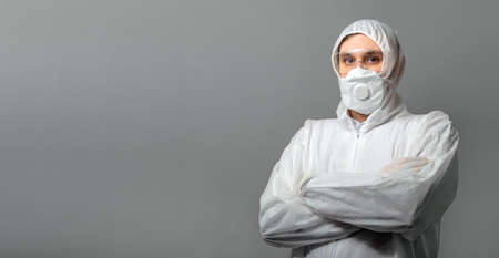 Coronavirus, covid-19 disinfection. Portrait caucasian doctor in protective medical suit, biological hazard, medical mask FFP3, goggles isolated on gray background. Doctor in chemical protection clothing for prevention virus spread.
