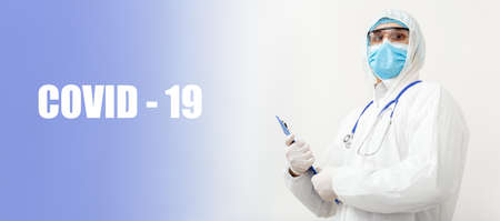 Covid-19 text and portret of Doctor in protective medical suit, biological hazard, face mask doctor with stethoscope writes on tablet. Medical healthcare concept Coronavirus, COVID, pandemic.
