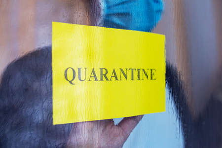 Quarantine text on yellow warning sign in window. Lonely man with Coronavirus, Covid-19 in self quarantine isolation in protective medical mask at home. Medical, healthcare social distancing concept Foto de archivo