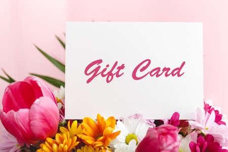 礼品券在花花束的在桃红色背景。礼品卡为女人提供优惠券。母亲节,母亲节,女儿或奶奶的母亲节,生日快乐或周年快乐的凭证