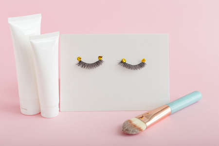 White tubes with mock up for design. False eyelashes, makeup brush on pink background. Beauty products, cosmetics for eyes makeup, eyelash extensions, beauty shop or salon concept. Banque d'images