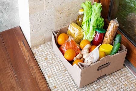 Food delivery or Donation Box during covid quarantine. Contactless social home delivery, safe shopping in coronavirus pandemic. Takeout meal. Food box on doorstep near door. Courier home delivery.