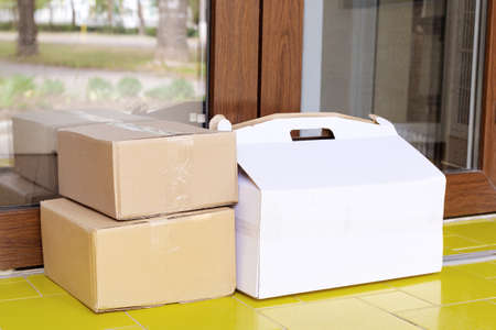 Delivery boxes on doorstep at home. Contactless food delivery. Safe shopping E-commerce purchase parcels at home. Boxes delivered to front door by courier, postman. Banco de Imagens