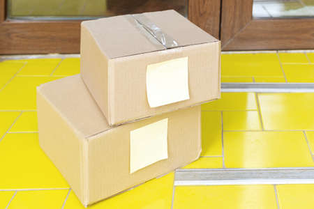 Delivery boxes on doorstep near home door. Contactless food delivery. Safe shopping E-commerce purchase parcels at home. Boxes delivered to front door by courier, postman. Imagens