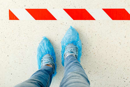 Woman stand in line keeping social distance wearing overshoes, medical shoe covers in hospital.Top view man standing behind a warning line during covid 19 coronavirus. Social distancing. Legs in line.