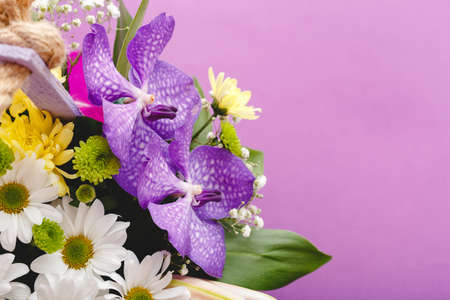 Beautiful bouquet of flowers in lilac wooden basket on purple background. Orchids, chrysanthemums, lilies, chamomiles floral floristic composition. Greeting card with copy space.