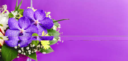 Beautiful bouquet of flowers in lilac wooden basket on purple background. Orchids, chrysanthemums, lilies, chamomiles floral floristic composition. Greeting card web banner with copy space. 免版税图像