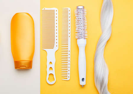 Shampoo, strand lock of blonde hair, different combs on color background. Dyed colored hair, hairdresser haircut beauty salon services. Hair care products for spa treatments. Banque d'images