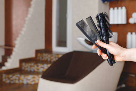 Black combs for hair cut in female hairdresser hand against hair wash sink chair in beauty salon, beauty studio, barber shop interior. Professional hair stylist hairdresser tools equipment.