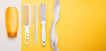 Shampoo, strand lock of blonde hair, different hair combs on color background. Dyed colored hair,hair care, hairdresser haircut beauty salon services. Long web banner with place for text.