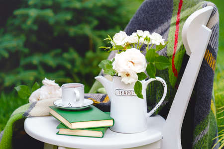 Cup of tea on books, flowers white wild rose in vase teapot, warm plaid on white chair outside in summer garden. Romantic provence leisure breakfast in garden with nature background.