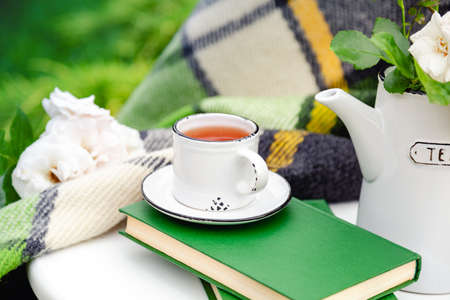 Summer breakfast in garden. Cup of tea on books with green warm plaid, spring flowers on white table outdoor