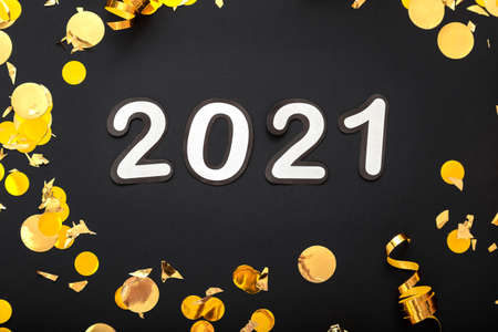 2021 white numbers text lettering in golden confetti, Christmas festive decor frame on black background. Happy New year event composition. Close up.