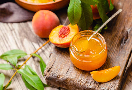 Peach jam in glass jar with peach wedges and whole fruit. Peach jam on wooden table. Canned fruit jam with ingredients.