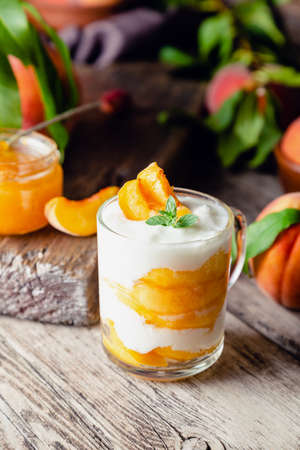 Peach fruit dessert in glass cup on rustic wooden table with fresh peach fruit, peach jam. Homemade dessert with fruits. Fruit salad with yogurt or sour cream