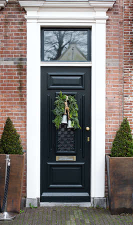 House facade with vintage front door decorated with christmas wreath with bells. Black vintage door with festive christmas decor. Porch European style in brick house