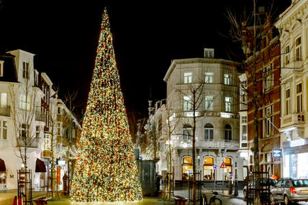 Maastricht, NETHERLANDS - December 25, 2019: Christmas tree decorated with lights on central square. Night city on Christmas and New Years Eve. Christmas Fair European christmas Editorial