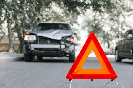 Red emergency stop triangle sign on road in car accident scene. Broken SUV car on road at traffic accident. Car crash traffic accident on city road after collision Banco de Imagens