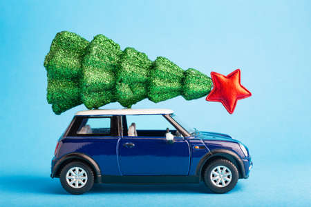 Christmas New Year tree with red star on top of blue car toy roof. Blue color background. Creative miniature Xmas tree on car