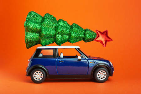 Christmas New Year tree with red star on top of blue car toy roof. Orange background. Creative miniature Xmas tree on car