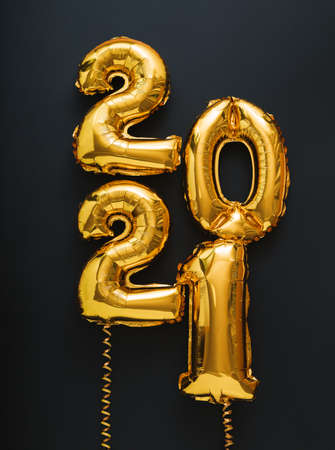 2021 balloon gold text on black background. Happy New year eve invitation with Christmas gold foil balloons 2021. Vertical