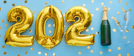 2021 golden air balloon numbers on blue background bottle of champagne and glasses with confetti. Happy New year eve invitation card with Christmas gold foil balloons 2021. Flat lay long web banner Banco de Imagens