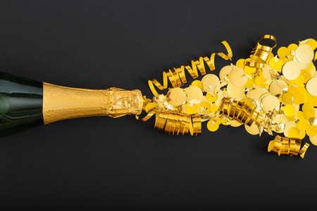 Golden bottle of champagne spills out gold sparkles on black background. Champagne sparkles explosion. Flat lay New Year eve celebration dark backdrop Banco de Imagens - 159940108