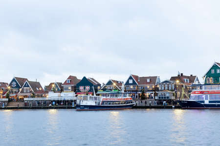 VOLENDAM, NETHERLANDS - December 24, 2019: Dutch harbor with city views, boats, Christmas decorations. Winter evening in traditional old town, Dutch fishing village. Banco de Imagens - 159983116