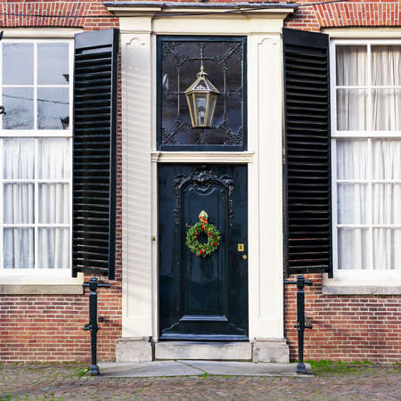 Christmas porch with christmas wreath and street light. House facade with vintage front door, antique shuttered windows. Black vintage door with festive christmas decor. European style brick house Banco de Imagens - 159940117
