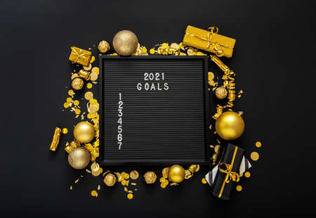 Numbered list of 2021 Goals on black Board in frame made of gold festive decor gift boxes confetti. New year eve 2021 goals, resolution check list with motivation. Flat lay square Copy space