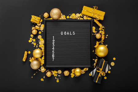 Numbered list of 2021 Goals on black Board in frame made of gold festive decor, gift boxes, confetti. New year eve 2021 goals, resolution check list with motivation or wishlist. Flat lay Copy space Banco de Imagens