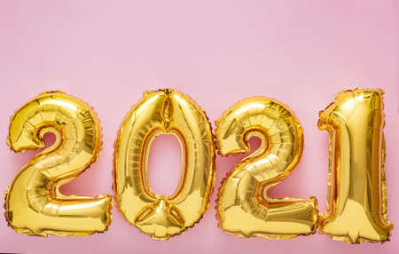 2021 air balloon gold numbers on pink background. Christmas Happy New year eve decor with gold foil balloons 2021 Copy space Top view