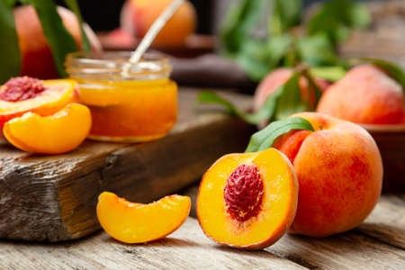 Peaches with leaves on dark wooden board with peach in halves with peach seed stone. Composition with ripe juicy peaches Harvest for food. Fresh organic fruit Banco de Imagens