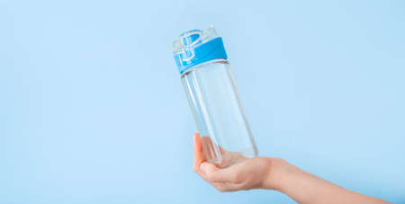 Water bottle in female hand. Reusable drinking water bottle for sports on blue backgraund. Healthy lifestyle and fitness concept. Long web banner with copy space