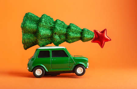 Odessa Ukraine 06 12 2019: Christmas New Year tree with red star on top of green car toy roof. Orange background. Creative miniature Xmas tree on car Editorial