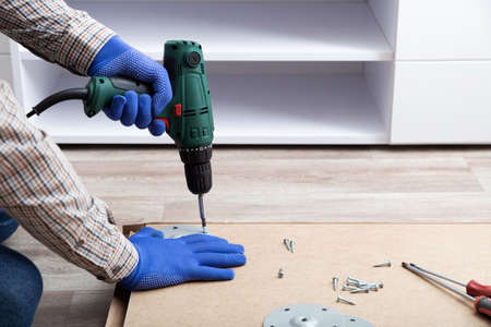 Man in gloves assembles table furniture with drill. Assembly, furniture repair home master. Male hand with drill on floor. Copy space.