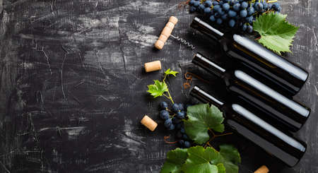 Wine bottles, grapes, grape bunches with leaves and vines corkscrew wine corks on dark rustic concrete background. Flat lay wine composition with copy space on black stone table. Long web banner Banco de Imagens