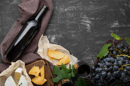 Wine bottle Camembert cheese and aged cheese, grapes. Wine bar snacks. Wine composition on dark rustic concrete background. Flat lay with copy space