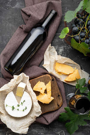Red wine bottle Camembert cheese and aged cheese, grapes. Wine bar snacks. Wine composition on dark rustic concrete background. Flat lay vertical crop