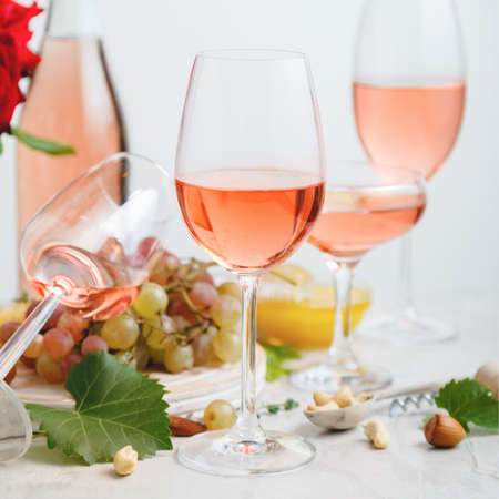 Rose wine in different types of glasses on light concrete background with grapes. Wine composition with nuts and grapes on white table. Square crop