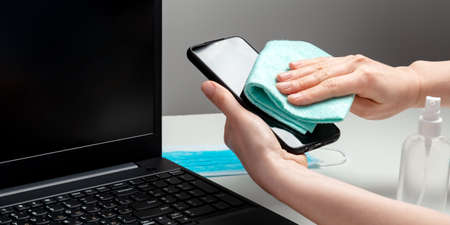Female hands disinfect phone screen and laptop keyboard by alcohol disinfectant. Protection hygiene prevention from infection, germs, bacteria by disinfectant during covid 19. Long web banner.