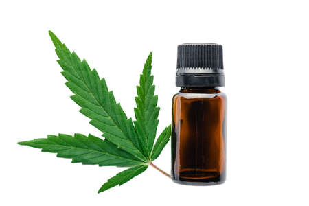 Hemp oil essential oil in black glass bottle with cannabis leaves isolated on white background. Cannabis leaf with skincare cosmetic product Banco de Imagens