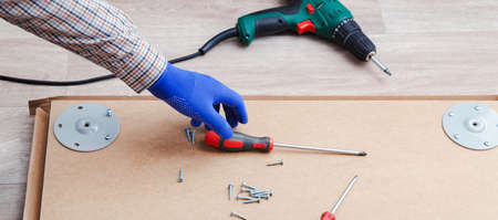 Furniture assembly process by male hands in gloves, master collects table furniture using screwdriver tools, drill instrument. Moving, home improvement, furniture repair renovation. Long web banner