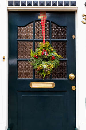 Vintage front door decorated with festive decor Christmas wreath on red tape. Traditional Christmas european exterior in Netherlands
